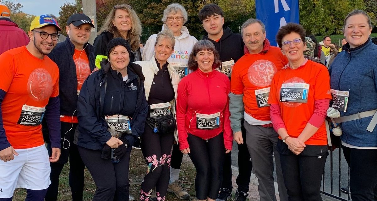 A smiling group of OT volunteers at the Scotiabank Waterfront Charity Race